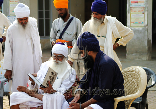 Gurdev Nidar Singh Nihang discussing his book with the revered Nihang elder, Baba Daya Singh Bidhi Chandia at Sursingh, India